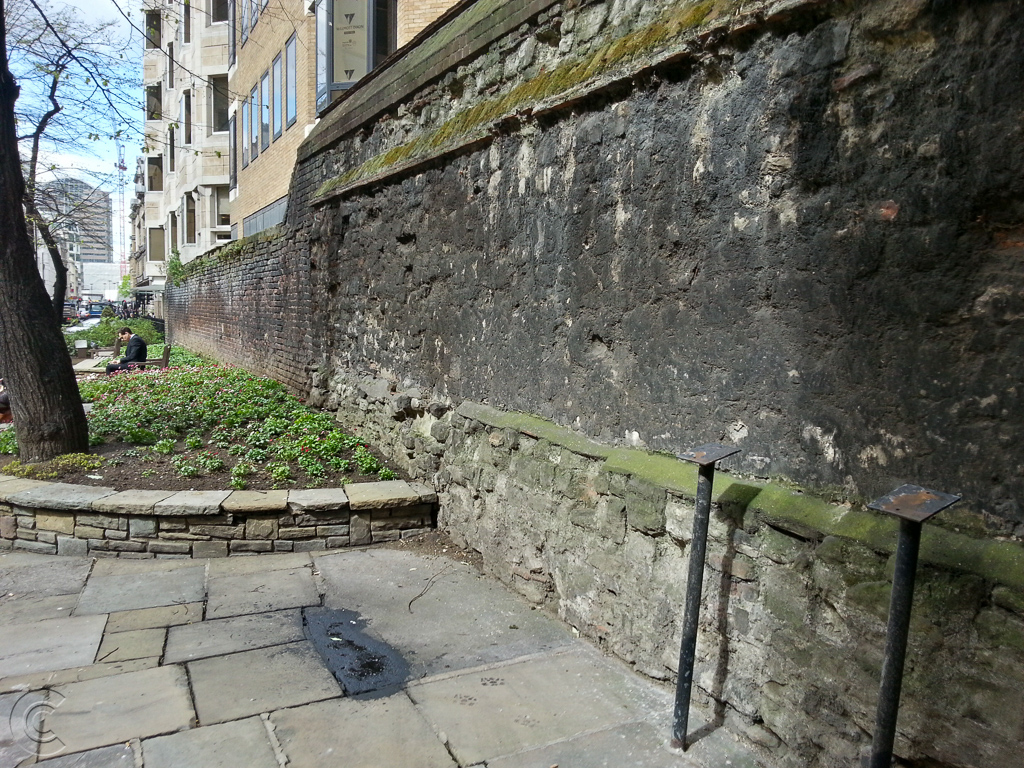 Looking west along Medieval wall at All Hallows churchyard. The tiled information panel is gone, but it's legs remain in the foreground.